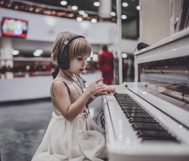 girl playing piano with headphones on