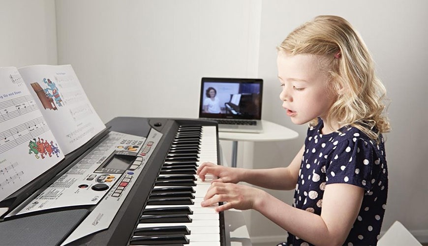girl playing keyboard on video lesson