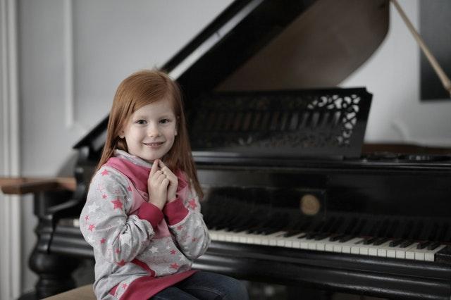 girl sat at piano