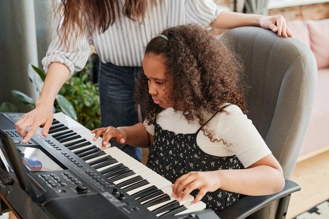 piano tutor demonstrating to student