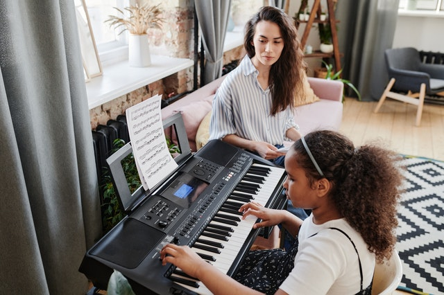 girl practicing piano with tutor