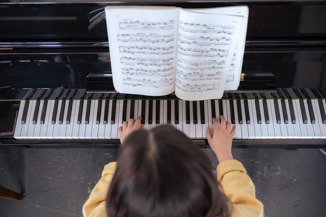 girl playing piano with sheet music