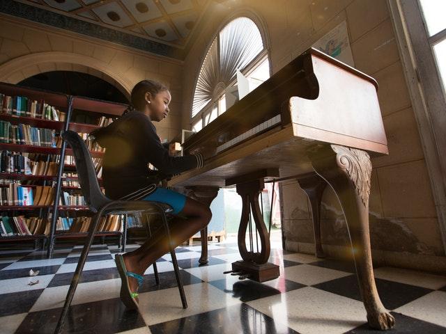 young girl sat at piano