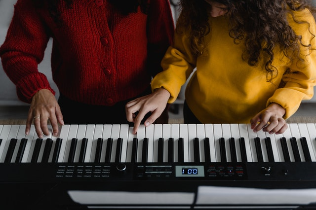 tutor playing keyboard with student
