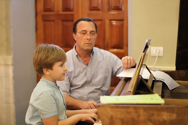 boy playing piano with tutor