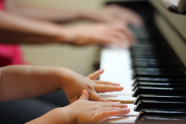 student playing piano with tutor
